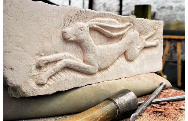 Stone carving a leaping hare carved in relief artison